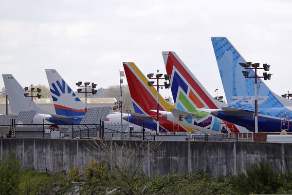 A line of Boeing 737 MAX jets sit parked on the airfield adjacent to a Boeing production plant Monday, April 20, 2020, in Renton, Wash. Boeing this week is restarting production of commercial airplanes in the Seattle area, putting about 27,000 people back to work after operations were halted because of the coronavirus. (AP Photo/Elaine Thompson)