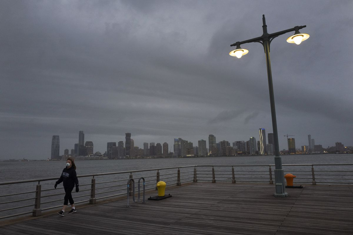 A woman wears a face mask as she walks on Pier 45 in Hudson River Park, Thursday night, April 30, 2020, in New York. As the new coronavirus pandemic upends lives across the United States, it is taking a widespread toll on people's mental health and stress levels, according to a survey that finds a majority of Americans felt nervous, depressed, lonely or hopeless in the past week. (AP Photo/Mark Lennihan)