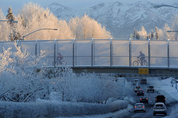 Cyclists cross a frosted overpass as the low-hanging sun brightens tree tops on Thursday, Jan. 5, 2017, in west Anchorage. (Erik Hill / Alaska Dispatch News)