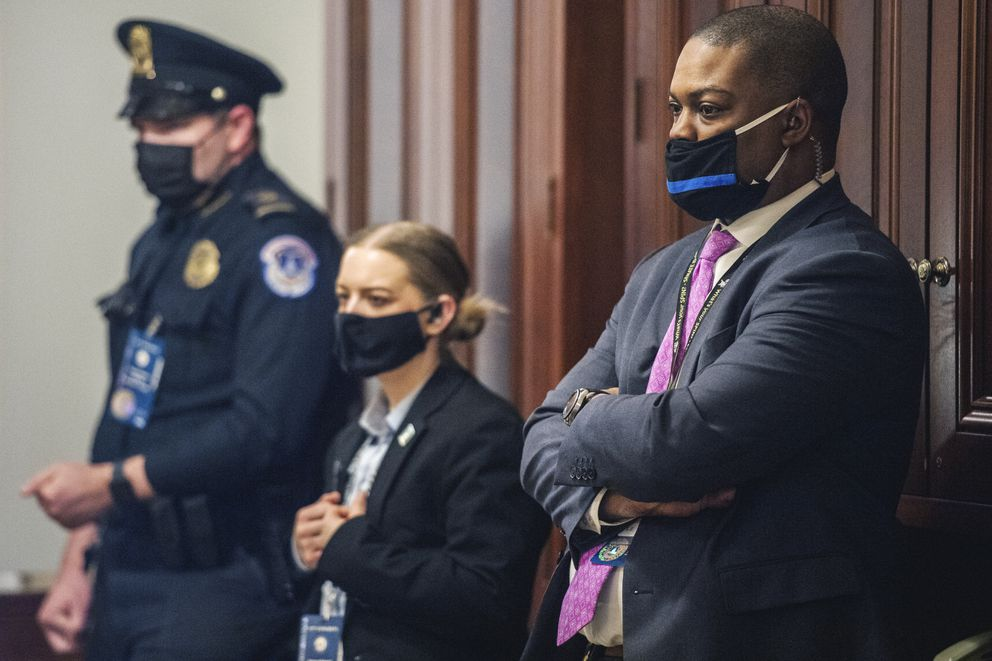 Capitol Police Officer Eugene Goodman, right, and other officers, watch never-before-seen security footage of rioters storming the Capitol on Jan. 6, during the second day of former President Donald Trump's second impeachment trial, Wednesday, Feb. 10, 2021 in the Capitol in Washington. (Brandon Bell/The New York Times via AP, Pool)