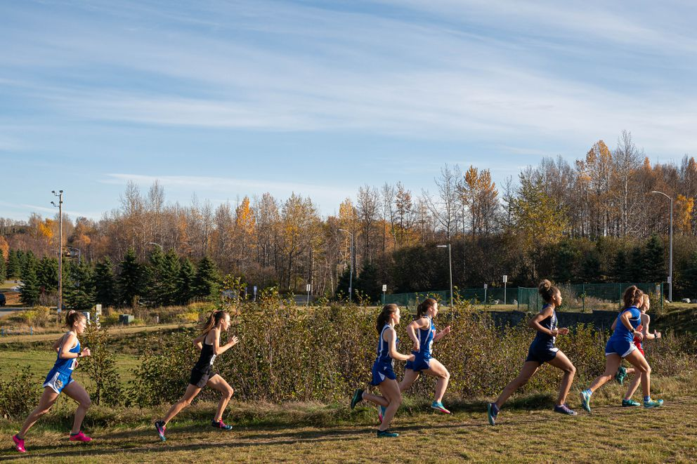 Division II girls run up a hill at the start of the state cross-country championship Saturday at Kincaid Park. (Loren Holmes / ADN)
