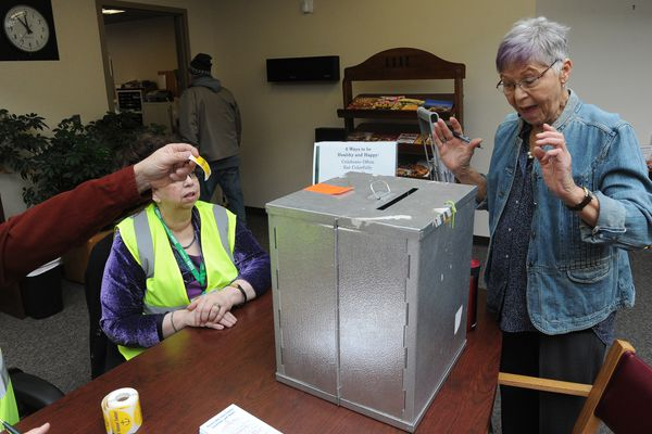 "Election worker Dean Cox hands Linda Jaco an ""I Voted Today!"" sticker after she cast her ballot in the municipal election at the Anchorage Senior Center in Anchorage, Alaska on Wednesday, March 28, 2018. Election worker Jean Sondrud looks on. (Bob Hallinen / ADN)"