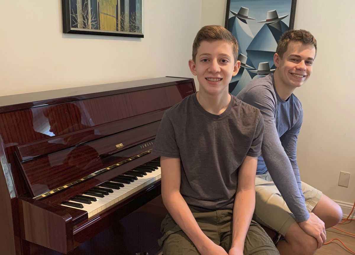 This Nov. 20, 2020 photo released by Andrea Fage shows brothers Rafael Fage, 16, background, ad Noah Fage, 14 posing at the piano at their home in Harrison, N.Y. During the pandemic lockdown, private piano lessons for boys stopped. They researched movie soundtracks and learned the score on their own with the assistance of sites like YouTube. (Andrea Fage via AP)