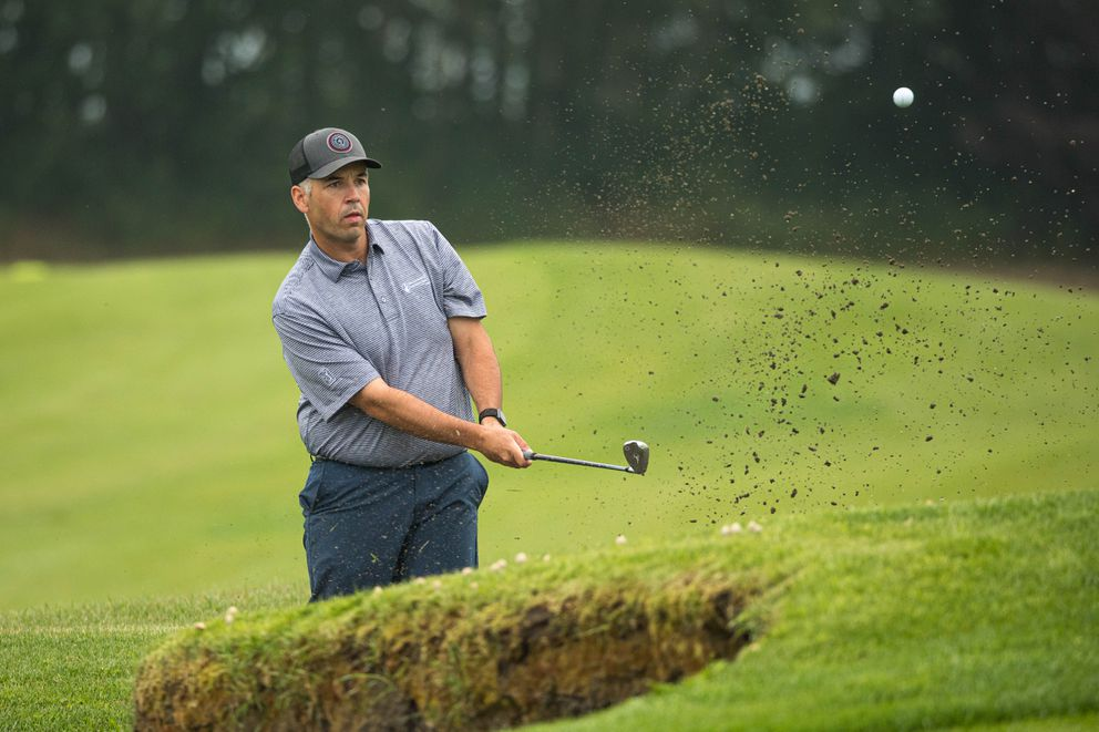 Adam Baxter chips the ball on his way to a 2-over 74. (Loren Holmes / ADN)