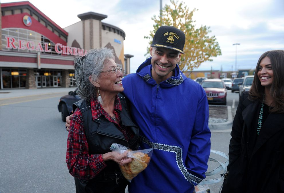 "Dee Olin shows her nephew Martin Sensmeier and his girlfriend Kahara Hodges some fry bread she made before the opening of ""The Magnificent Seven"" in Anchorage on Friday. (Bob Hallinen / Alaska Dispatch News)"