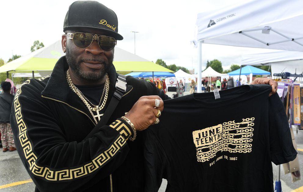 David (who only gave his first name) shows the T-shirt he got from the UAA Student Life Leadership booth at the Juneteenth Celebration on Saturday. (Bob Hallinen photo)