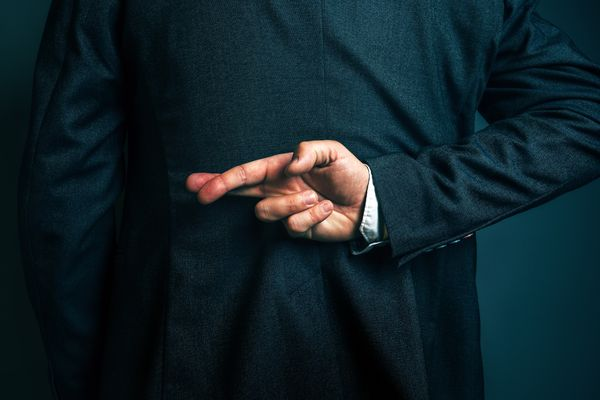 Dishonest businessman telling lies, lying businessperson holding fingers crossed behind his back. (Getty)