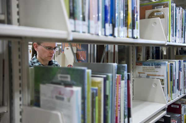Jody Young shelves books before the Loussac Library opens to the public on March 15, 2018. (Marc Lester / ADN)