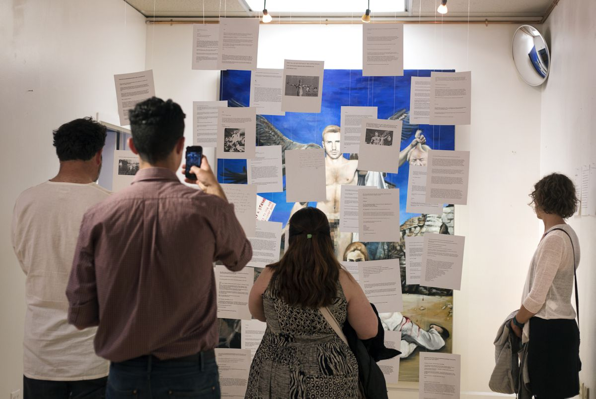 "Visitors look at the installation ""Everything"" by Thomas Chung at the ""Trumpazo!"" exhibit on Friday, June 2, 2017, in Anchorage. The controversial painting received backlash calling for its destruction and punishment for Chung. A barrier with printouts of these messages was created between the viewer and painting, acting as a way to expand the conversation. (Rugile Kaladyte / Alaska Dispatch News)"