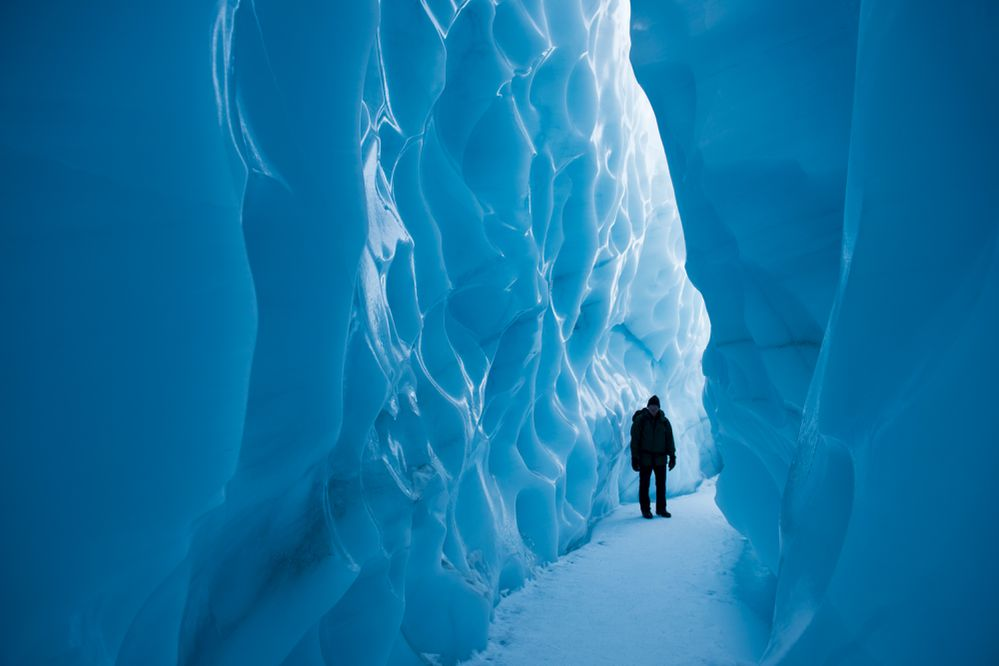 Matanuska Glacier Park guide and caretaker Bill Stevenson walks along a narrow slot of ice at the foot of Matanuska Glacier on February 23, 2017. Matanuska Glacier Park now requires first-time winter visitors to take a $100 guided tour. (Marc Lester / Alaska Dispatch News)