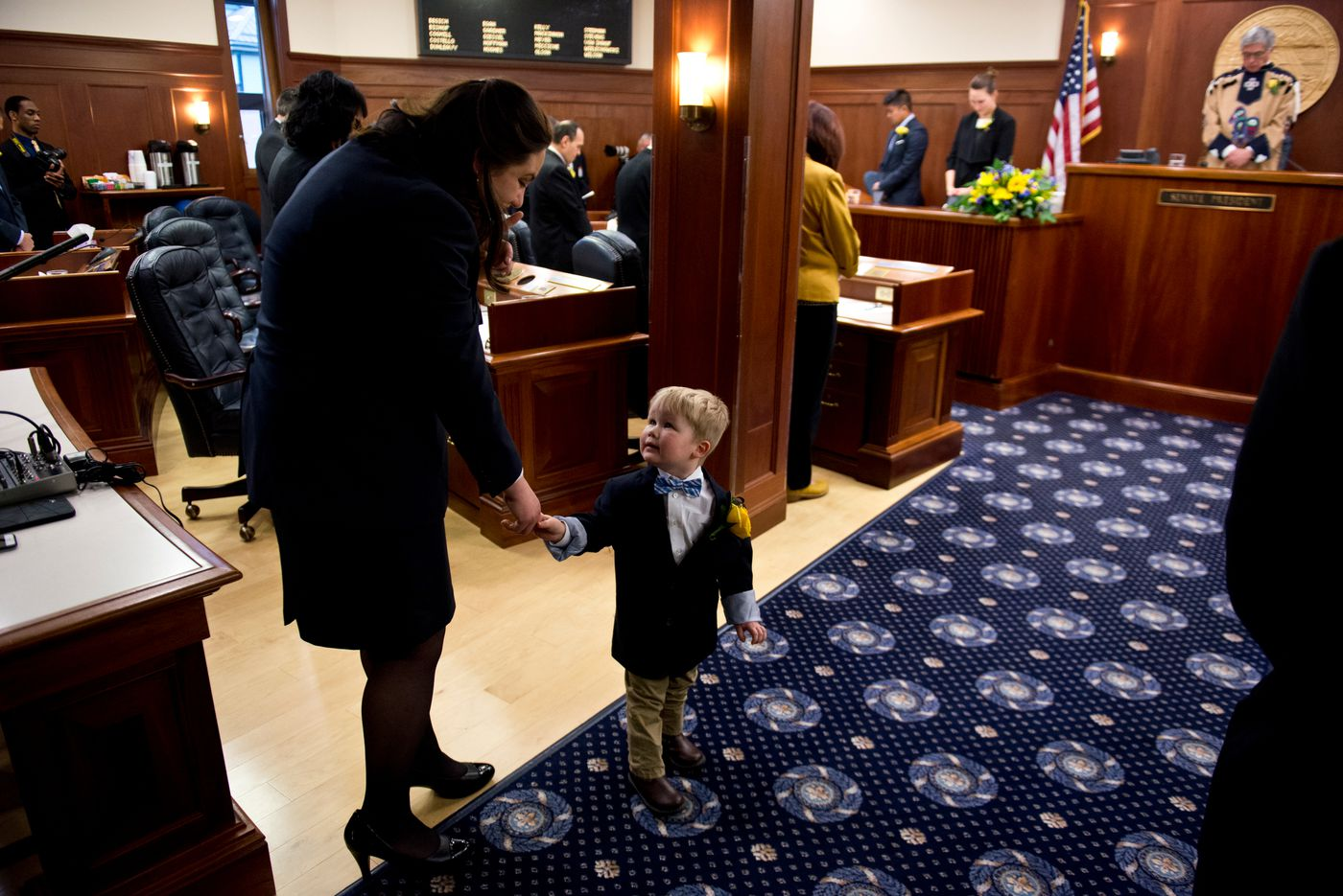 Mason Fairclough, 2, grandson of Sen. Anna MacKinnon, holds hands with a Senate page during an invocation.