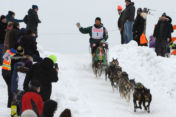 Blayne Streeper waves to the crowd gathered at 15th Avenue and Cordova Street hill en route to winning his eighth Fur Rondy Open World Championships on Sunday, March 1, 2020. (Bill Roth / ADN)