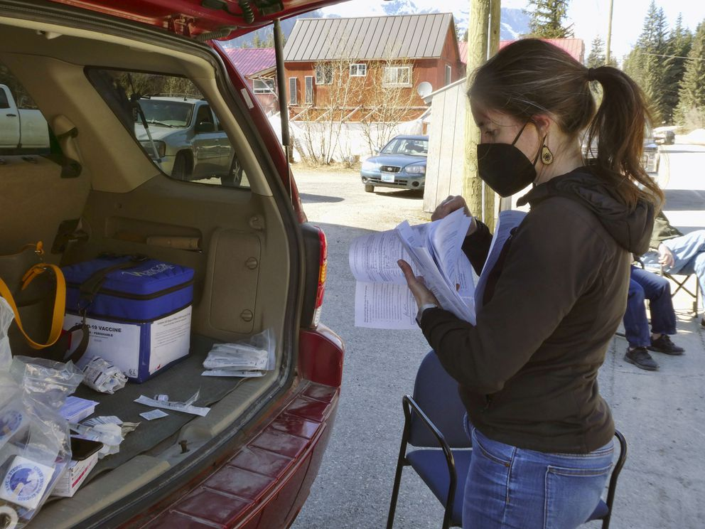 Alaska's chief medical officer, Dr. Anne Zink, flips through paperwork after a COVID-19 vaccine clinic in Hyder, Alaska, on Thursday, April 22, 2021. (AP Photo/Becky Bohrer)