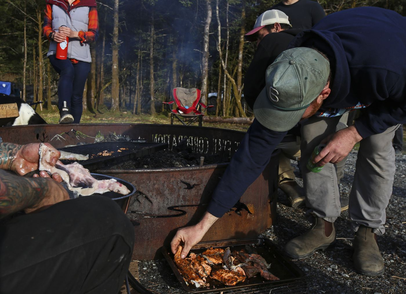 Michael Hand grabs a piece of Copper River king salmon from a tray before it is moved to a table at Hartney Bay in Cordova on Tuesday, May 18, 2021. (Emily Mesner / ADN)