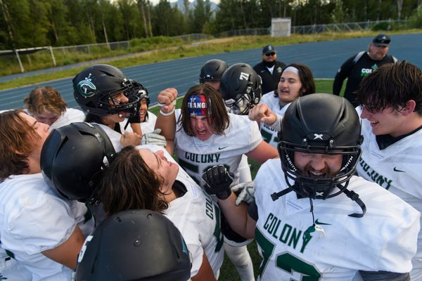 Colony players huddle for a cheer at halftime. Due to COVID-19 related concerns, the visiting team did not have a locker room to use at halftime. Colony beat Palmer, 49-0, in the opening football game of the season on August 21, 2020. (Marc Lester / ADN)