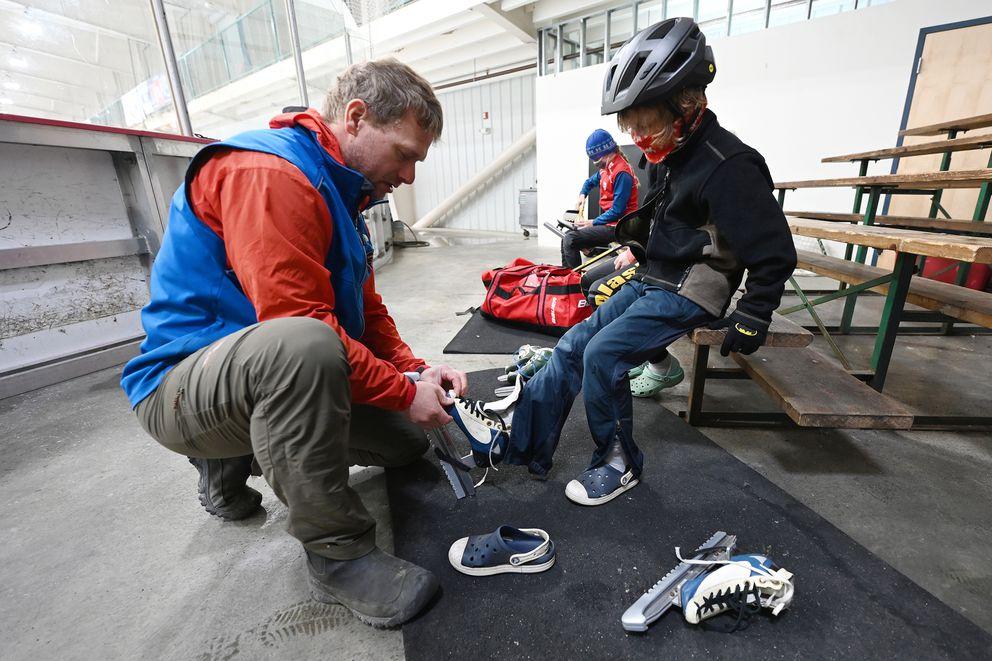 Alaska Speedskating Club president Carl Oswald helps Trogon Hauser put on skates. (Bill Roth / ADN)