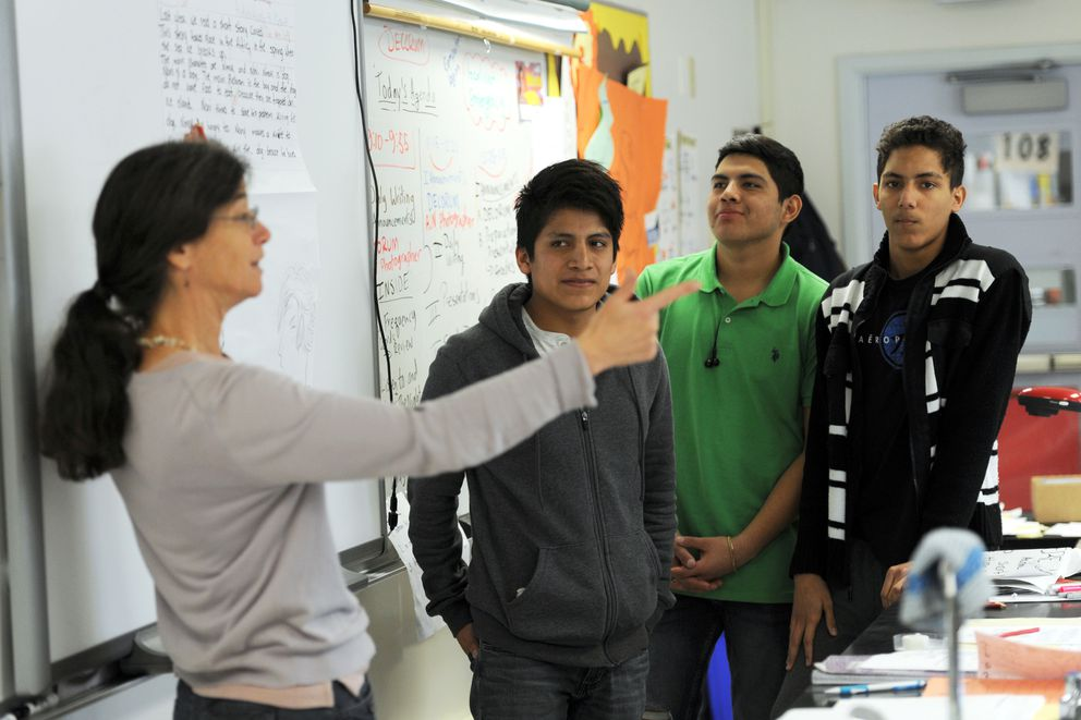Teacher Jessica Stern, left, solicits input from her class as Rosendo Martinez from Mexico, Juan Gutierrez from Mexico and Kendry Castillo from the Dominican Republic present their group writing assignment for critique on Sept. 30 at Wendler Middle School. (Erik Hill / Alaska Dispatch News)