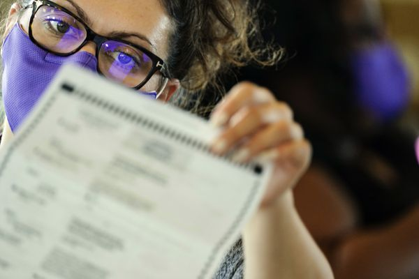 An election worker examines ballots as vote counting in the general election continues at State Farm Arena on Thursday, Nov. 5, 2020, in Atlanta. (AP Photo/Brynn Anderson)