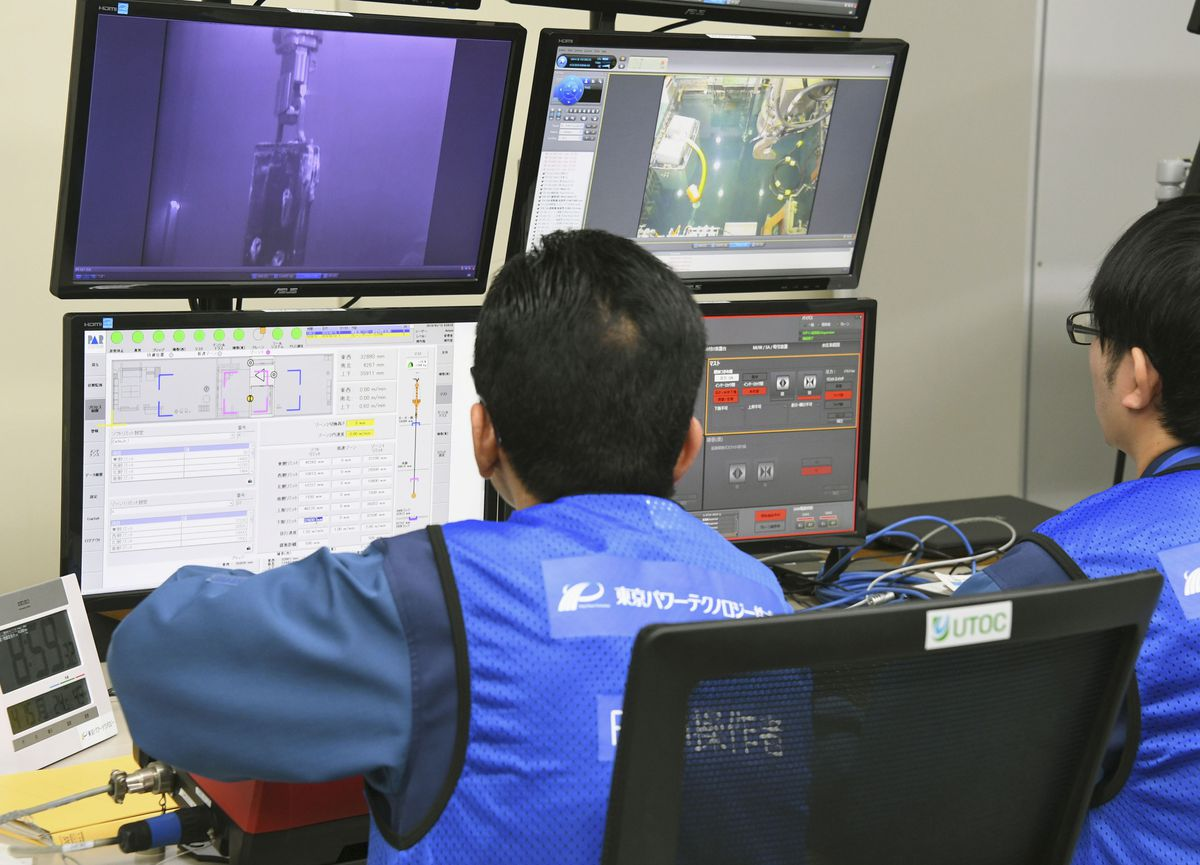 Tokyo Electric Power Co. workers remotely make operation for removing fuels at Unit 3 of Fukushima Dai-ichi nuclear plant, in Okuma, Fukushima Prefecture, northeastern Japan Monday. April 15, 2019. (Kyodo News via AP)