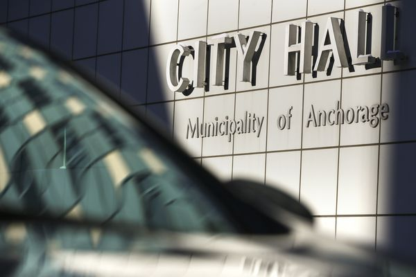 City Hall is reflected in the window of a car parked outside the building in downtown Anchorage on Friday, Feb. 12, 2021. (Emily Mesner / ADN)
