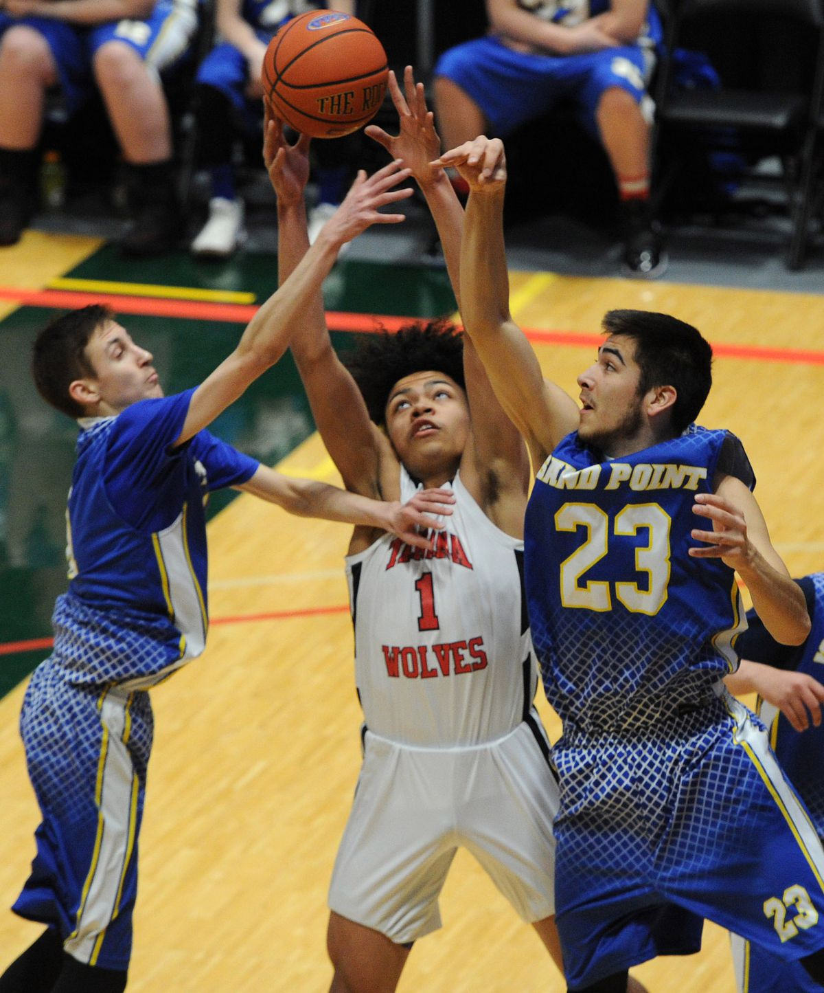 Tanana eighth-grader Malachi Bradley battles for a rebound against Sand Point's Parker Larsen and Karl Smith during Tanana's 86-47 quarterfinal victory. (Bill Roth / ADN)