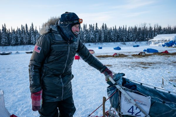 John Schandelmeier tends to his team in Nikolai on Wednesday, March 11, 2020 during the Iditarod Trail Sled Dog Race. (Loren Holmes / ADN)