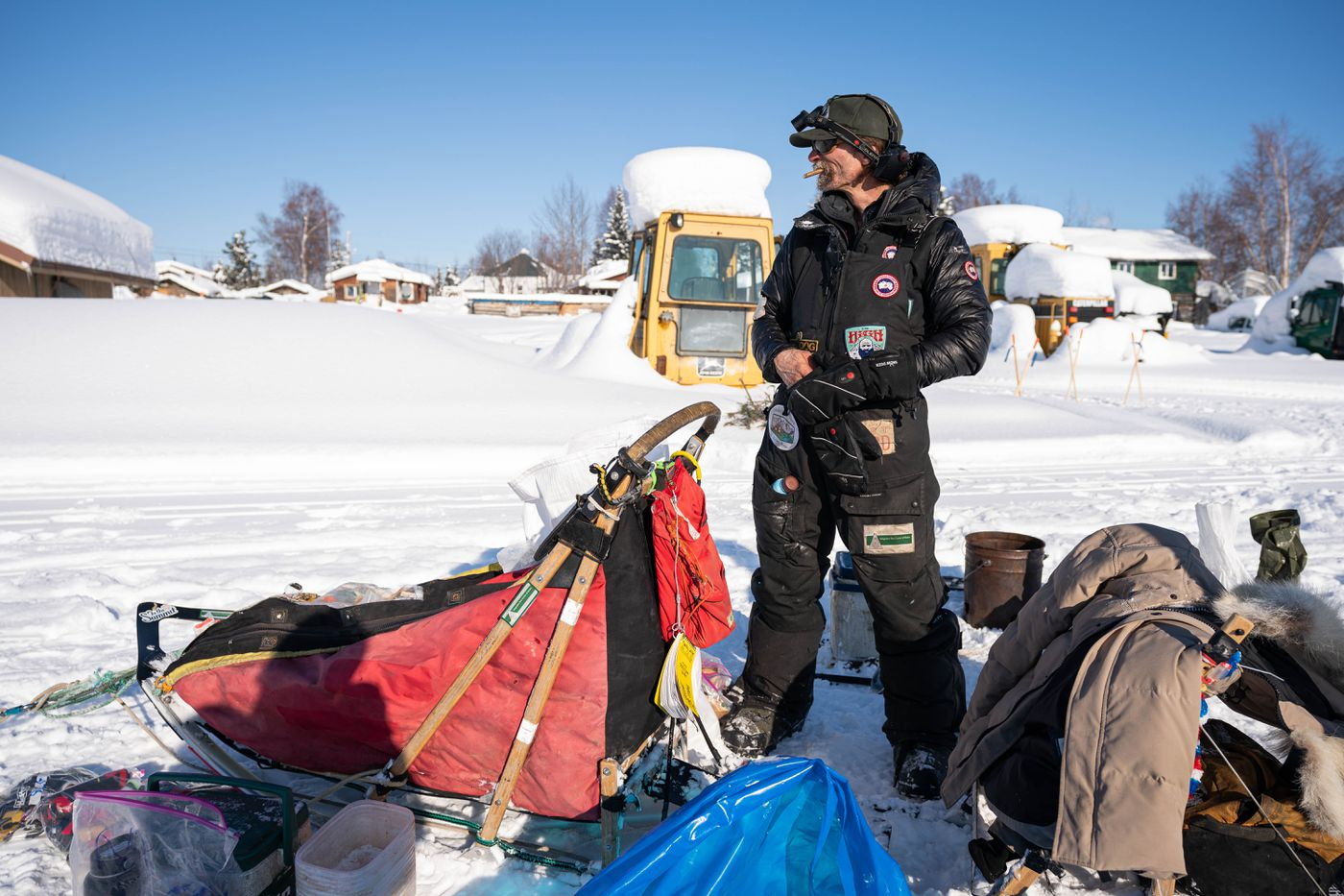 MARCH 10. Lance Mackey smokes a cigar while tending to his team in Nikolai during the Iditarod Trail Sled Dog Race. (Loren Holmes / ADN)