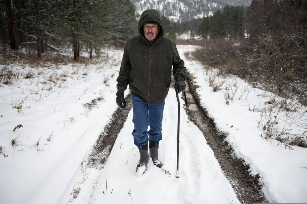Richard King, 70, walks down a muddy road on the family ranch near Zortman, Mont., on Sunday, Dec. 8, 2019. 'It's called complete serenity. ' King said of living on the ranch. 'Its close as you can get to God living here. ' (AP Photo/Tommy Martino)
