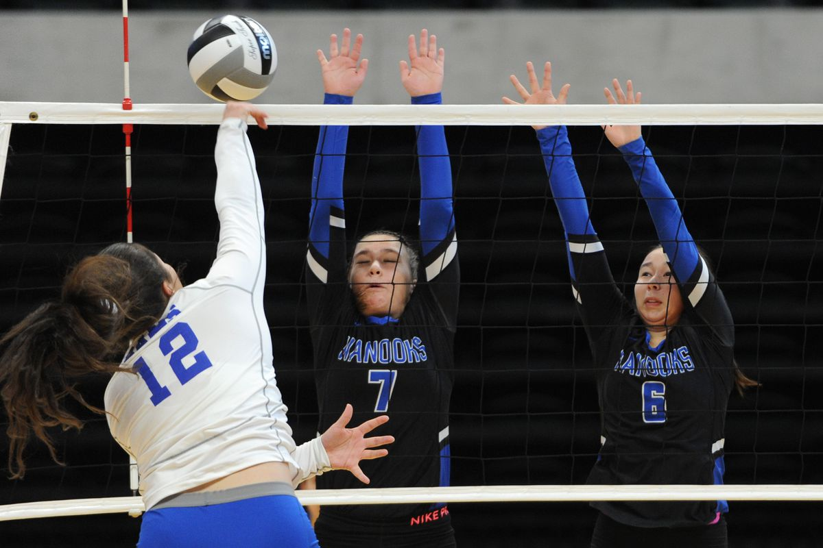 Monroe sophomore Madelaine Muramoto (12) hits the ball against Nome blockers Courtney Merchant (7) and Amber Gray (6) Thursday at the Alaska Airlines Center. (Bill Roth / ADN)