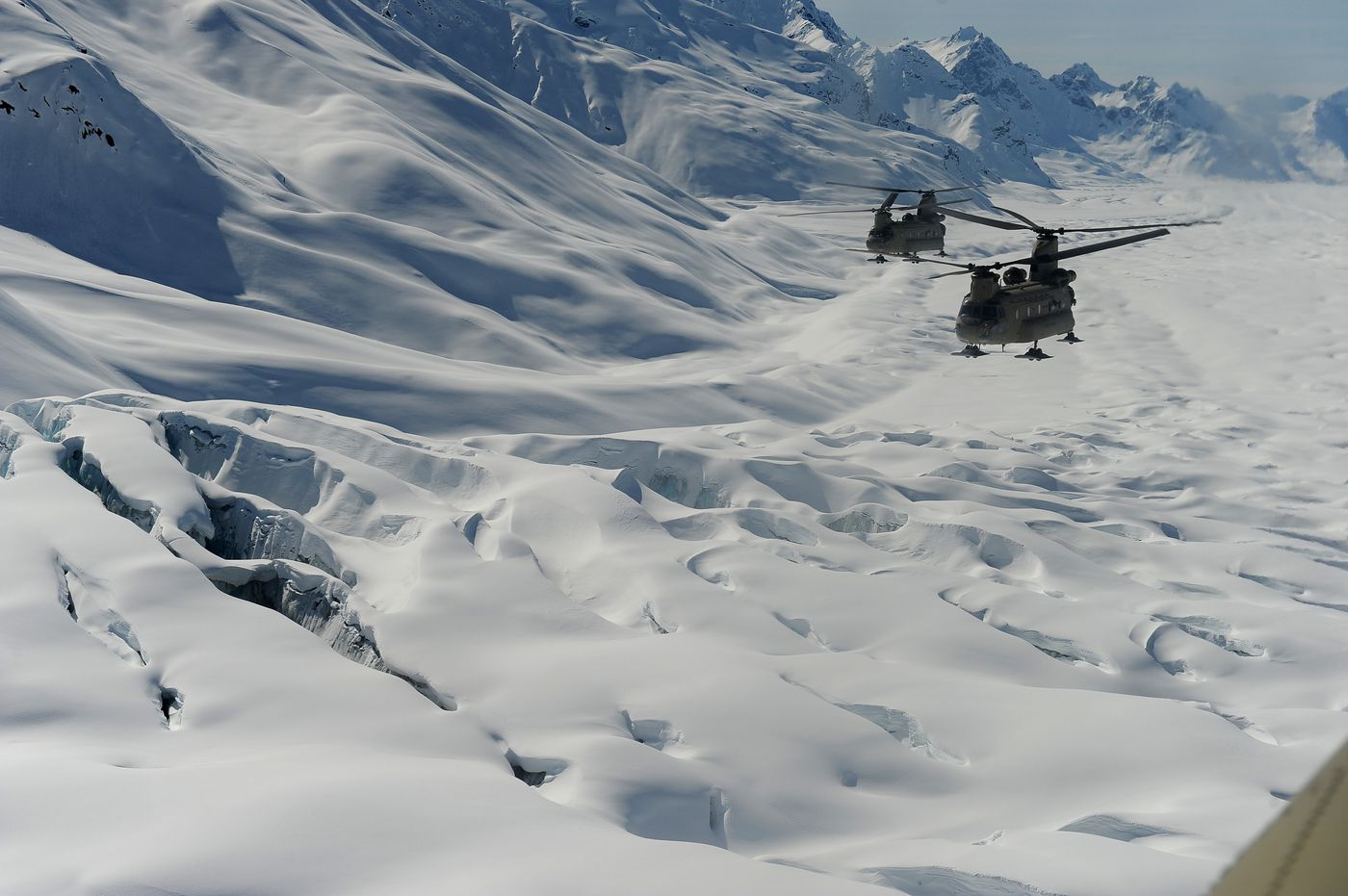 Two Chinook helicopters pass over a crevasse field as Fort Wainwright soldiers haul tents, fuel and food up to Kahiltna Glacier for the National Park Service's Denali mountaineering camp on Sunday, April 24, 2016.