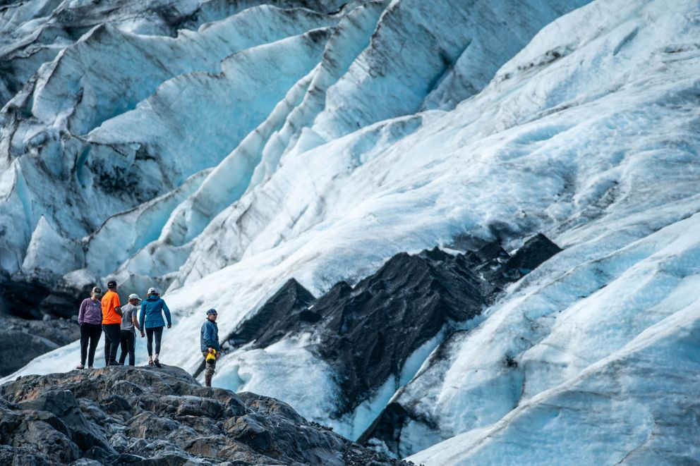 People stand on a rock near the face of Portage Glacier on Saturday, June 13, 2020. (Loren Holmes / ADN)