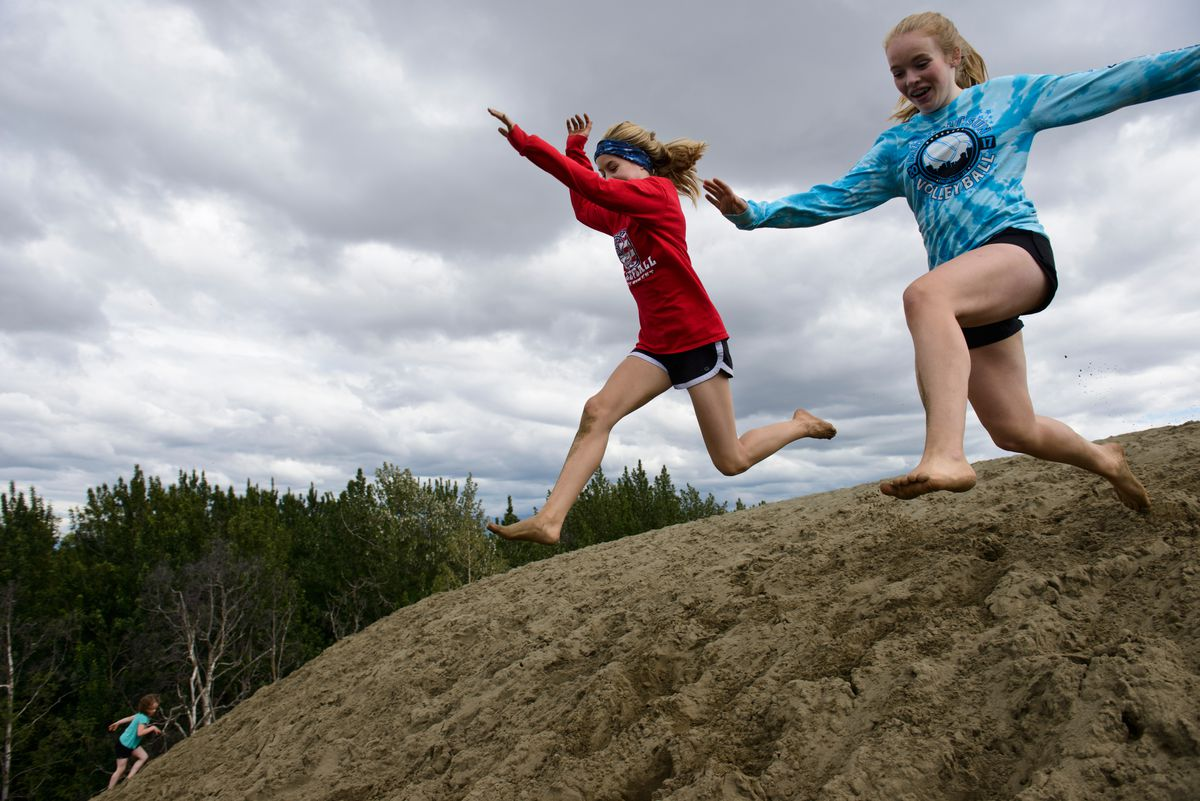 Shyla Lacy, 13, and Matti Loffredo, 14, compete to see who can leap farther down the soft slope of a hill last summer at the Kincaid Park sand dunes. (Marc Lester / ADN)