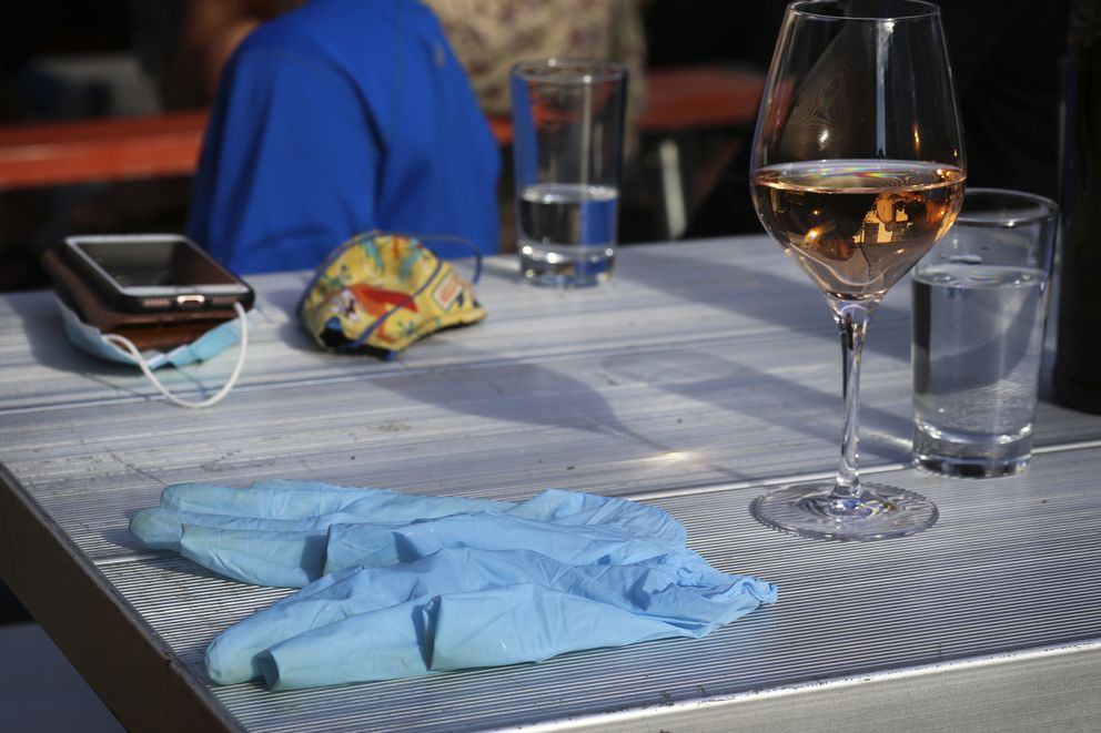 Used gloves rest next to a wine glass on a table in the outdoor dining area on G Street in Anchorage on Aug. 7, 2020. (Emily Mesner / ADN)