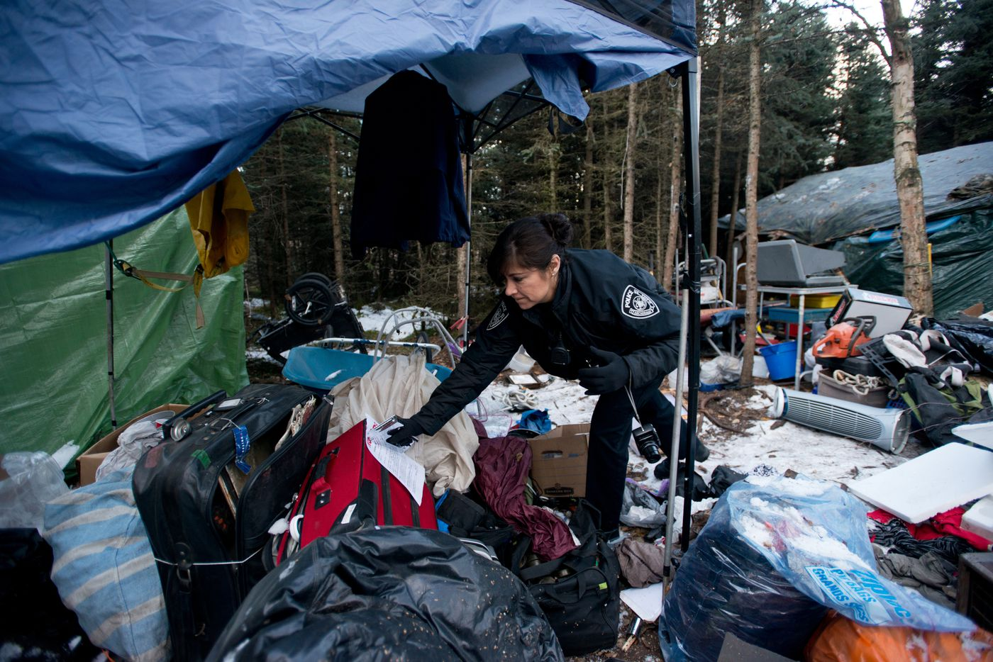 "Anchorage Police officer Sally Jones posts a notice at a homeless camp in the woods near 46th Avenue and Bering Street in Anchorage. The sign notifies campers that all items at the illegal camp may be removed in 15 days. Jones says she has mixed feeling about her ability to get chronically alcoholic people off the streets. ""We're dispersing the problem. What we're trying to do as a police department is, 'Okay, you have a problem. You need to get assistance',"" she said. ""The problem is, a lot of these people don't want it. They just don't want to follow the rules. They want to live for free."" Photographed on Friday, November 7, 2014. Marc Lester / ADN"