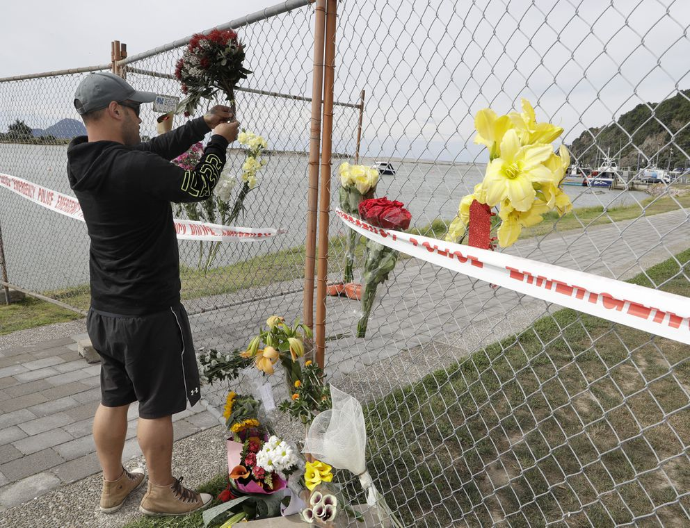 A man places a bouquet to a fence on the waterfront in Whakatane, New Zealand, Tuesday, Dec. 10, 2019. Unstable conditions hampered rescue workers from searching for at least eight people missing and feared dead after a volcano off the New Zealand coast erupted on Monday Dec 9 in a towering blast of ash and scalding steam while dozens of tourists explored its moon-like surface. (AP Photo/Mark Baker)