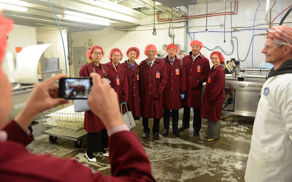 A delegation from the World Trade Center in Harbin, China, has their photo made during a tour of the Copper River Seafoods plant in Anchorage June 8. (Bob Hallinen / ADN)