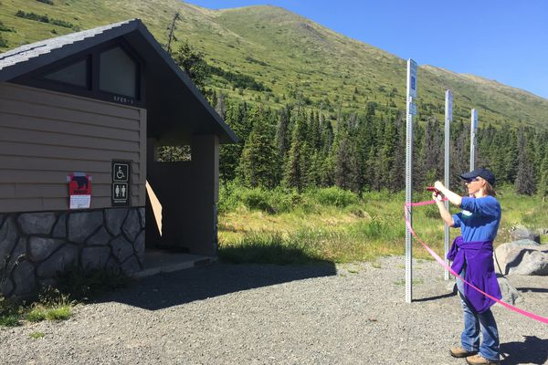 Kristen Pettit of Lisle, Illinois takes a photo of a closure sign at the South Fork Eagle River trailhead on Thursday, July 19, 2018. Pettit and her family planned to hike the trail Thursday morning, but chose a different hike after learning of the trail closure. (Matt Tunseth/Alaska Star)