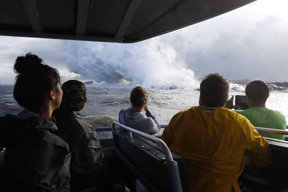 FILE - In this May 20, 2018 file photo, people watch a plume of steam as lava enters the ocean near Pahoa, Hawaii. Officials say an explosion sent lava flying through the roof of a tour boat off the Big Island, Monday, July 16, 2018, injuring at least 13 people. The people were aboard a tour boat that takes visitors to see lava from an erupting volcano plunge into the ocean. (AP Photo/Jae C. Hong, File)