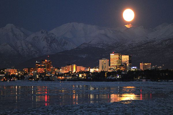 The biggest Supermoon of the year backlights spindrift from a north wind in the Chugach Mountains while rising over the Anchorage skyline and reflecting off an outgoing tide on Tuesday evening, Feb. 19, 2019. (Bill Roth/ ADN)