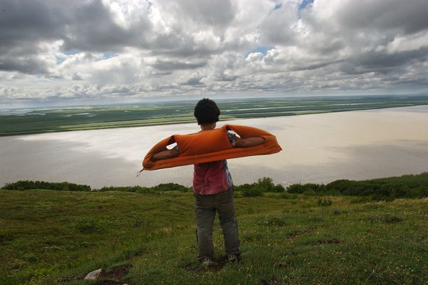 Edward Prunes, 11, catches the wind while taking in a view of the Yukon Delta atop Azachorok Mountain following a short hike from his home in Mountain Village in 2005. (Erik Hill / ADN)