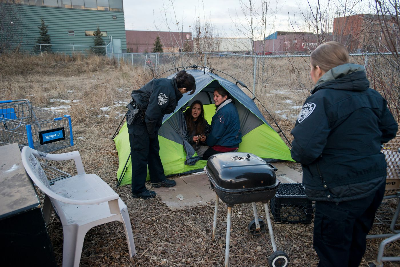 Anchorage Police officers Sally Jones, left, and Natasha Welch talk with campers in an empty lot on 33rd Avenue in Midtown. The campers were warned about trespassing, but Jones said they'd have until the following morning to clear out. Photographed on Friday, November 7, 2014. Marc Lester / ADN