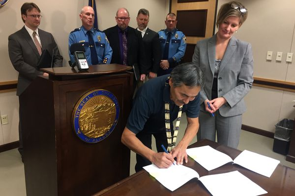 Carl Jerue Jr., first chief of the tribal government of Anvik near the Yukon River in Western Alaska, signs a landmark agreement with Alaska Attorney General Jahna Lindemuth that will allow the village's tribal court to prosecute low-level criminal offenses that had been previously handled by the state, Tuesday, Jan. 10, 2017. The deal was heralded as a money-saver for Alaska and a model document for other tribes seeking similar agreements. (Alex Demarban / Alaska Dispatch News)