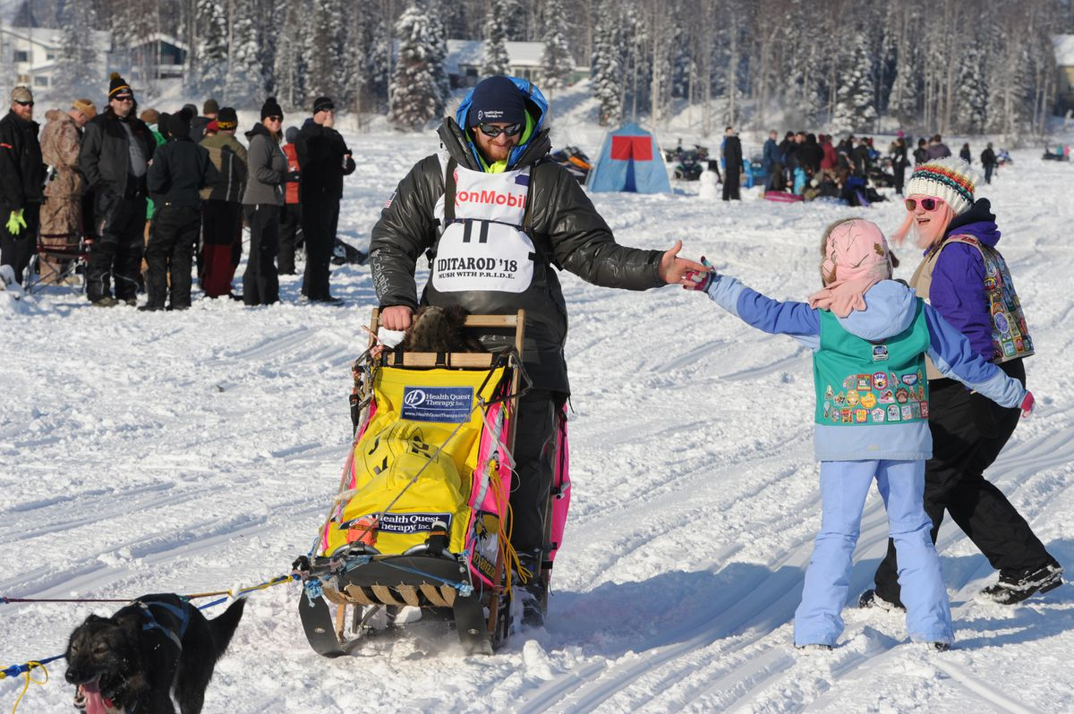 Wade Marrs high-fives spectators as he crosses Long Lake during the restart of the Iditarod Trail Sled Dog Race in Willow on Sunday. (Bill Roth / ADN)