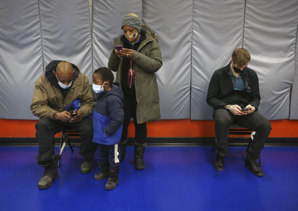 From left, Anthony Green, Theo Green, 4, Ayanna Green and Joshua Easterly wait along a gym wall and fill out an online vaccine form. (Emily Mesner / ADN)