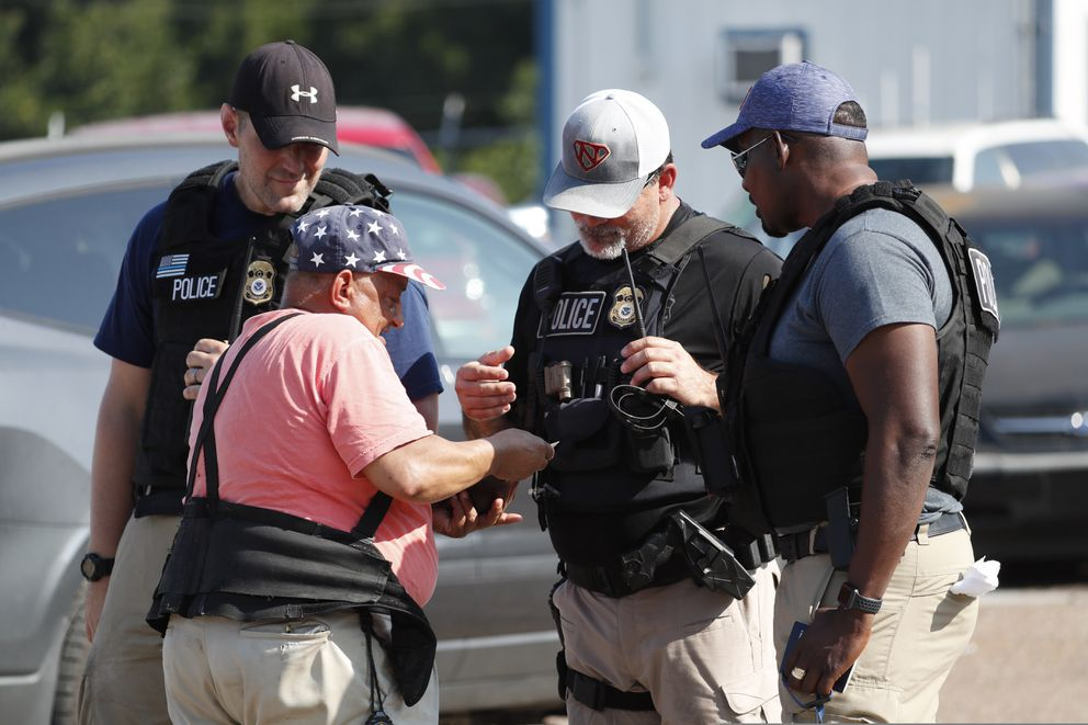 Domingo Candelaria, a registered immigrant, shows federal agents his identification as he prepares to leave the Koch Foods Inc., plant in Morton, Miss., following a raid by U.S. immigration officials, Wednesday, Aug. 7, 2019. The raid, one of several in Mississippi, was part of a large-scale operation targeting owners as well as undocumented employees. (AP Photo/Rogelio V. Solis)