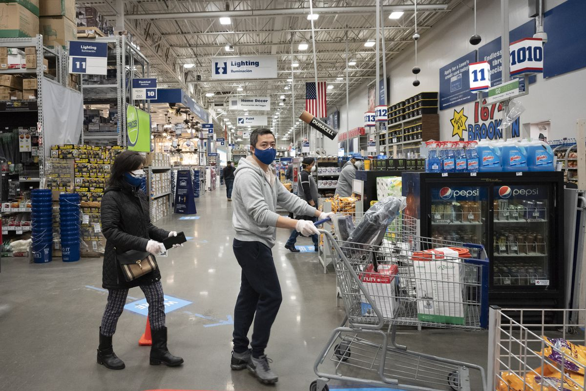Lowe's customers wear gloves and masks as they shop, Friday, April 3, 2020, during the coronavirus pandemic in New York. (AP Photo/Mark Lennihan)