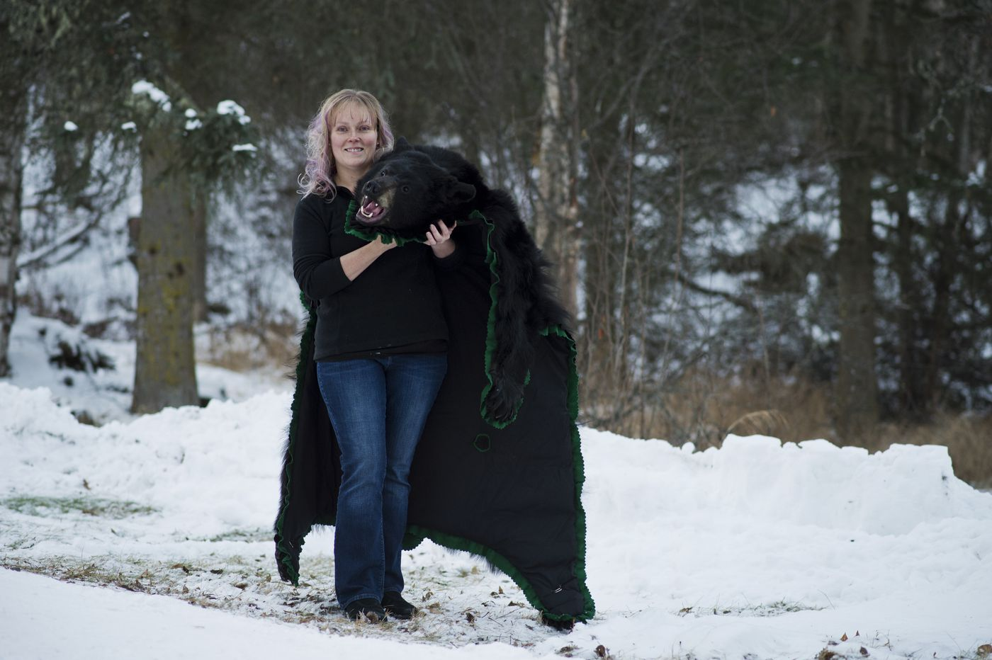 Taxidermist Andrea Radford holds a black bear rug outside her shop. (Marc Lester / ADN)