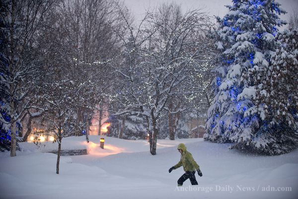 A pedestrian passes through snowy Town Square downtown. Anchorage woke up to a heavy snowfall on Wednesday, December 12, 2012. (Marc Lester / ADN archive)