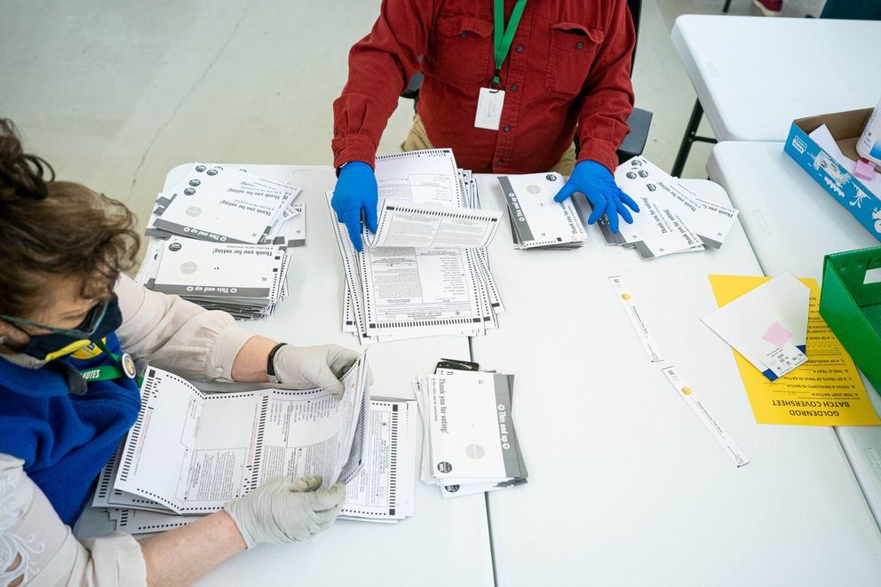 Election workers Jean Sondrud, left, and Marvin Cox unfold ballots so they can be scanned on Wednesday, April 7, 2021 at the Municipality of Anchorage election center. (Loren Holmes / ADN)