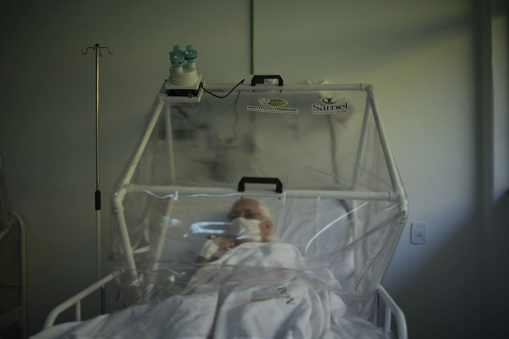An elderly COVID-19 patient is treated inside a non-invasive ventilation system named the Vanessa Capsule at a municipal field hospital Gilberto Novaes in Manaus, Brazil, Monday, May 18, 2020. The field hospital, set up inside a school, has nearly 150 beds and is operating near its limit as it treats patients both from the capital and remote Amazon areas. (AP Photo/Felipe Dana)